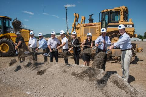 groundbreaking ceremony of Ecopax Inc manufacturing team wearing white safety helmets, shovelling dirt, and two yellow excavator truck