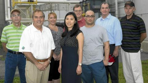 Christina Won Vice President of Operation at Ecopax posing pictures with Ecopax staff in front of their manufacturing plant in Lehigh Valley